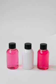 Mini bottles of pink and white color with body care cosmetics or hair on white background