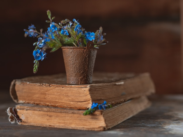 Mini bouquet of wild flowers in a decorative bucket on old books on the village window.