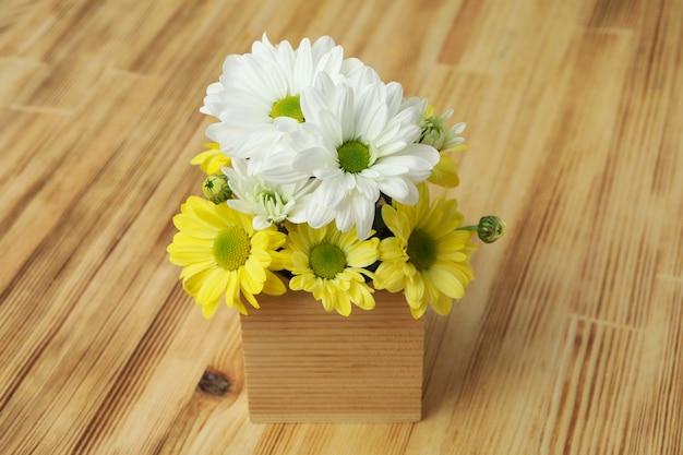木製の背景に菊のミニボックス。