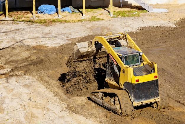 Мини-бульдозер работает с грунтовым грунтом при выполнении ландшафтных работ на строительстве