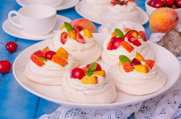 Mini cake pavlova with peaches and cherries decorated with mint leaves.