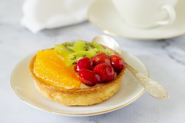 Mini cake or tart with custard and various fruits in jelly.