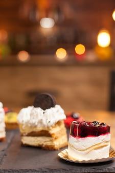 コーヒーショップで新鮮なベリーとバニラクリームのミニケーキ。天然素材を使った伝統的なデザート。コーヒーショップで美味しいチョコレートケーキ。