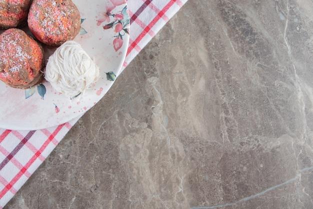 Мини-пирожные и турецкая сахарная вата в тарелке на кухонном полотенце на синем.