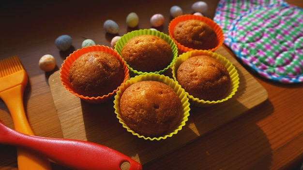 Mini cakes decorated with eggs, easter dessert. simple mini muffins in colorful silicone bakeware. kitchen and cooking concept on wooden background