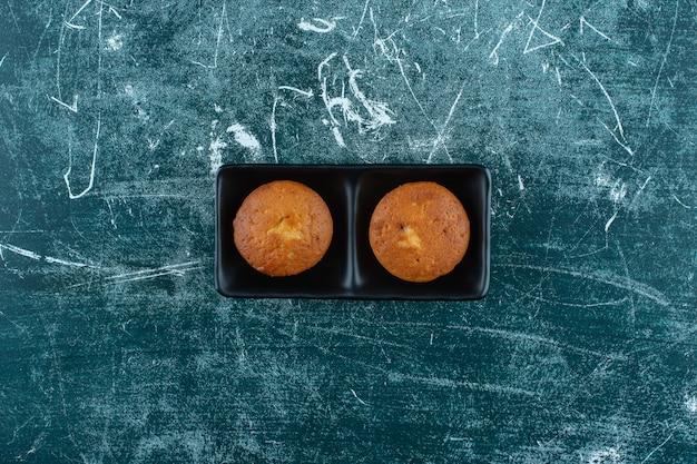 Mini torte in un piatto, sullo sfondo blu. foto di alta qualità