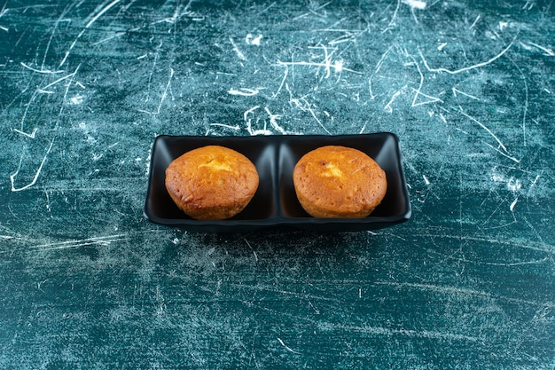 青い背景に、皿の中のミニケーキ。高品質の写真