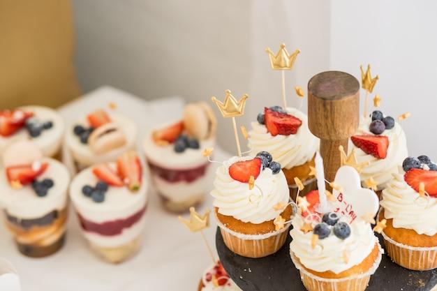 Мини торты. сладости для праздника. вкусный торт. маленькие пирожные с различными ягодами и ванильным кремом. миндальное печенье - сладкое безе на основе кондитерских изделий.