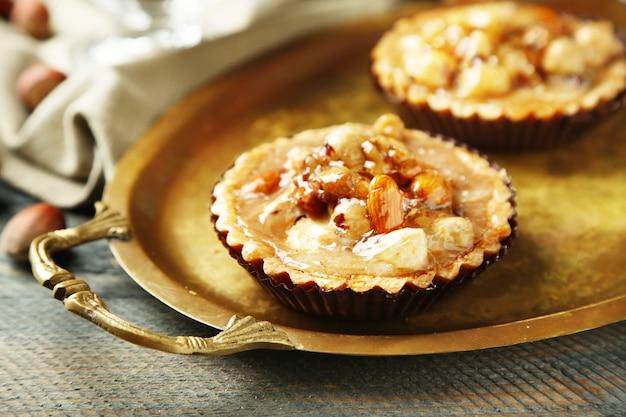 Мини-пирожные с орехами на салфетке на деревянном фоне