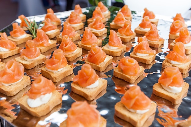 Mini canapes with smoked salmon on a silver platter for a party. mini canapes with smoked salmon
