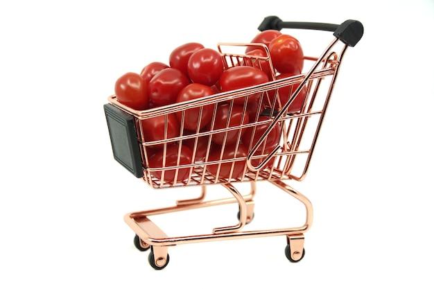 흰색 표면에 고립 된 빨간 체리 토마토와 미니 카트 쇼핑 및 음식 구매 은유 개념