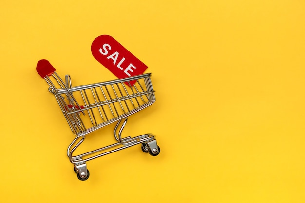 Mini cart with red coupon for discounts. the concept of sales and discounts of goods.