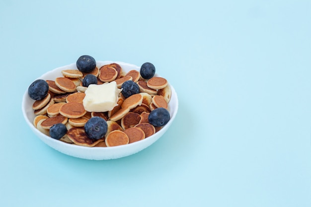 Mini cereal pancakes in boul on blue background