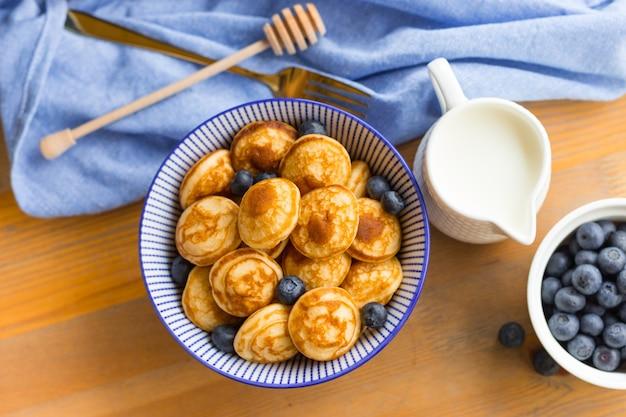 木製のテーブルにベリーとミニシリアルパンケーキ。トレンディな料理のコンセプト、子供のための朝食の時間。メニュー、レシピ、上面図またはフラットレイ