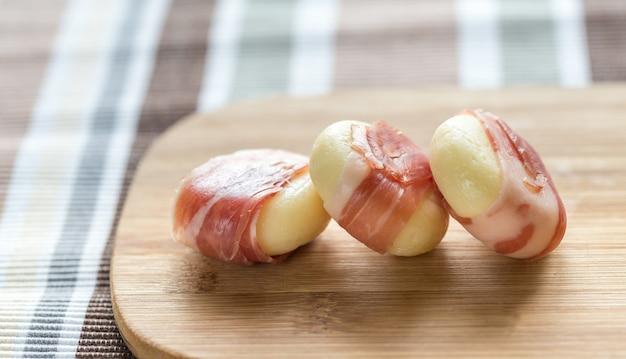 Роллы с сыром и прошутто на деревянной доске