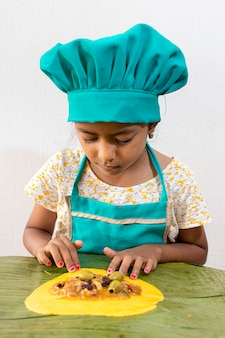 Mini chef preparing typical venezuelan hallacas