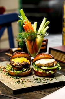 Vista laterale del mini formaggio della carota della lattuga del pomodoro del cetriolo dell'hamburger della carne e del pollo