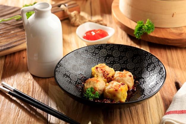 木製のテーブルの上の黒いボウルに唐辛子油とミニ中国点心