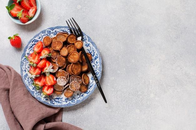 회색 콘크리트 테이블에 아침 식사를 위해 딸기와 미니 초콜릿 팬케이크 시리얼