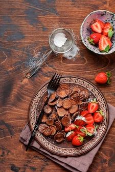 古い木製のテーブルで朝食にイチゴとミニチョコレートパンケーキシリアル。小さなパンケーキとトレンディな家庭の朝食。上面図。