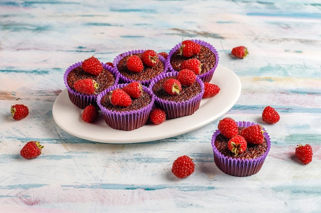 Mini chocolate sufle cupcakes with raspberries.