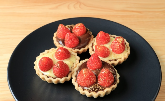 Mini chocolate tarts and cream tarts with fresh strawberries and edible gold powder