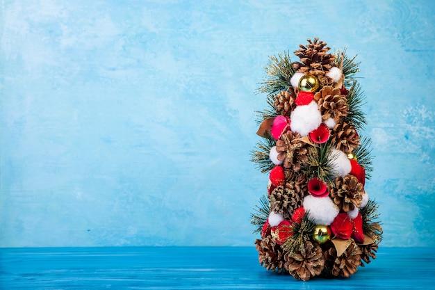 Mini albero di natale su sfondo blu in studio fotografico. stagionale e festivo