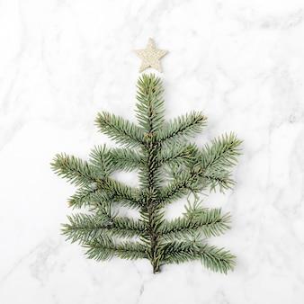 大理石の背景にモミの枝で作られたミニクリスマスツリー。新年のコンセプト。フラットレイ。