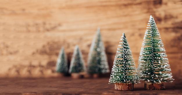 Мини-дерево из елки на деревенском деревянном столе и темно-коричневой стене из лиственной древесины