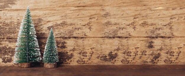 Мини-елка на деревенском деревянном столе и темно-коричневой деревянной стене