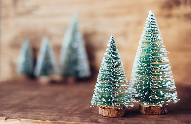 Mini christmas tree wood on rustic wooden table and dark brown hardwood wall