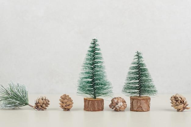 베이지 색 표면에 미니 크리스마스 트리와 솔방울