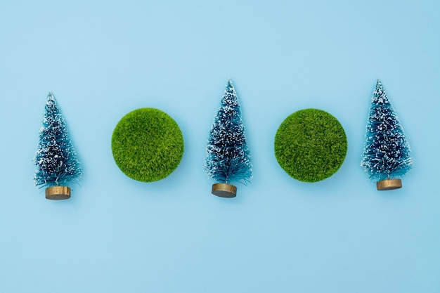 Mini christmas trees and green balls on blue background. christmas and new year holiday concept. winter festive season. flat lay. copy space
