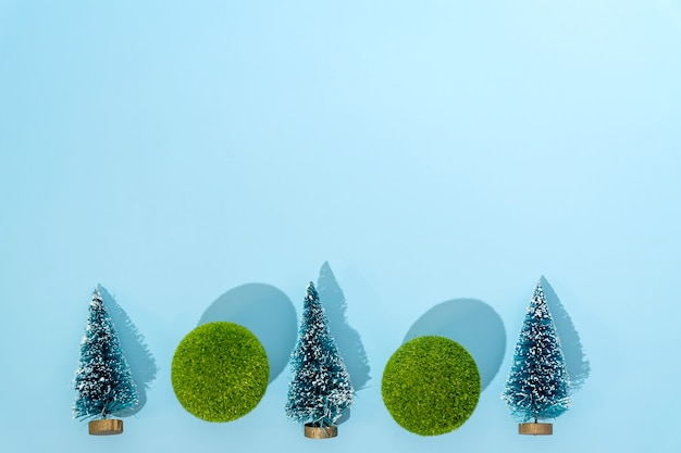 Mini christmas trees and green balls on blue background with copy space for text or design. christmas and new year holiday concept. winter festive season. flat lay.