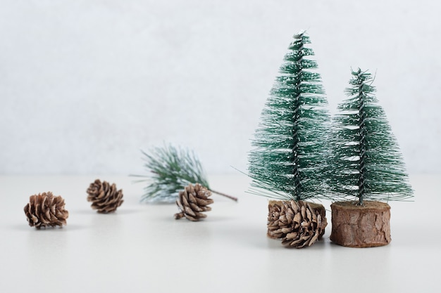 Mini christmas trees and pinecones on beige surface