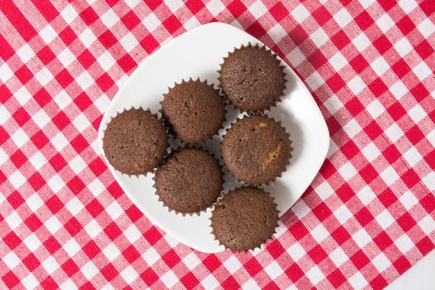 Mini cocoa muffins on white plate