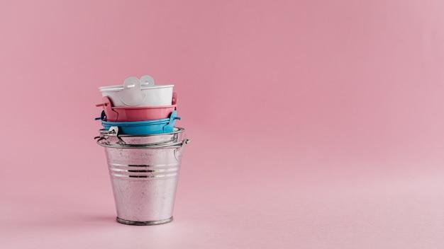 분홍색 벽에 미니 컬러 깡통 양동이 또는 양동이