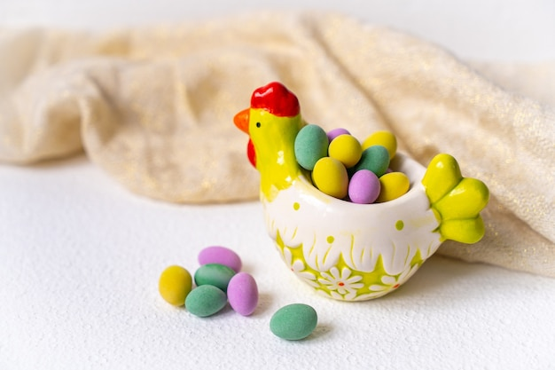 Mini colorful eggs inside a chicken shaped bowl over a white table with beige kitchen cloth