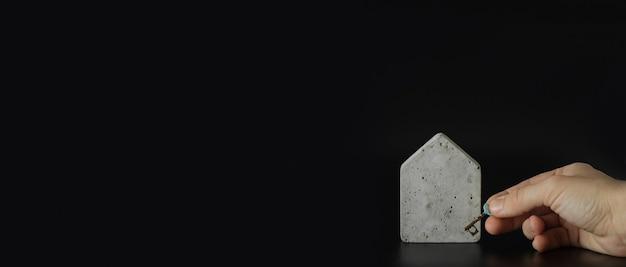 검은색 바탕에 열쇠가 있는 미니 콘크리트 집 모델과 손. 집을 사다. 부동산 사다리, 모기지 및 부동산 투자에 대한 개념입니다. 텍스트, 복사 공간, 현대적인 레이아웃을 위한 여유 공간.