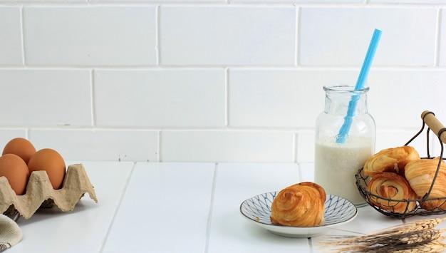 우유를 곁들인 미니 크로와상, 프랑스산 버터를 곁들인 바삭한 페이스트리. 화이트 주방에 접시와 짠 와이어 바구니에 제공. 텍스트를 위한 공간을 복사합니다.