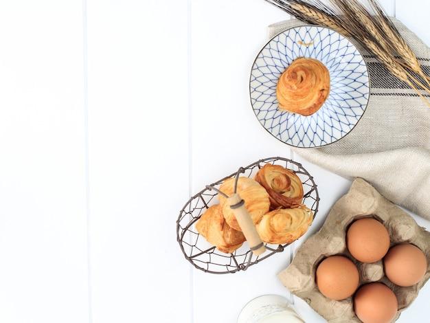 Мини-круассан с молоком, слоеное тесто с маслом по-французски. подается на тарелке и плетеной проволочной корзине на белой кухне.