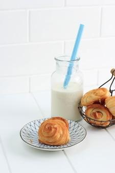 우유를 곁들인 미니 크로와상, 프랑스산 버터를 곁들인 바삭한 페이스트리. 화이트 주방에 접시와 짠 와이어 바구니에 제공.