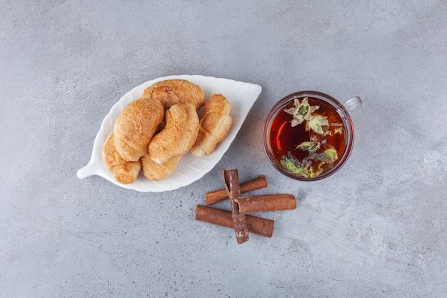 골든 크러스트와 차 한잔을 곁들인 퍼프 페이스트리로 만든 미니 크로와상.
