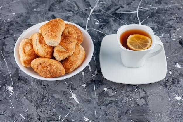 골든 크러스트와 차 한 잔을 곁들인 퍼프 페이스트리로 만든 미니 크로와상.