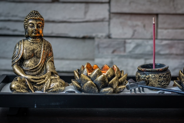 Mini, desk zen garden with lit candle and small buddha in it.