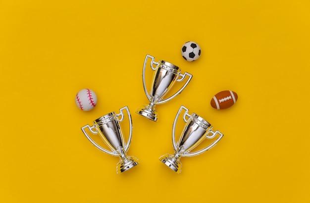 노란색 배경에 미니 다른 스포츠 공과 챔피언 컵. 미니멀리즘 스포츠 개념입니다. 평면도. 플랫 레이.