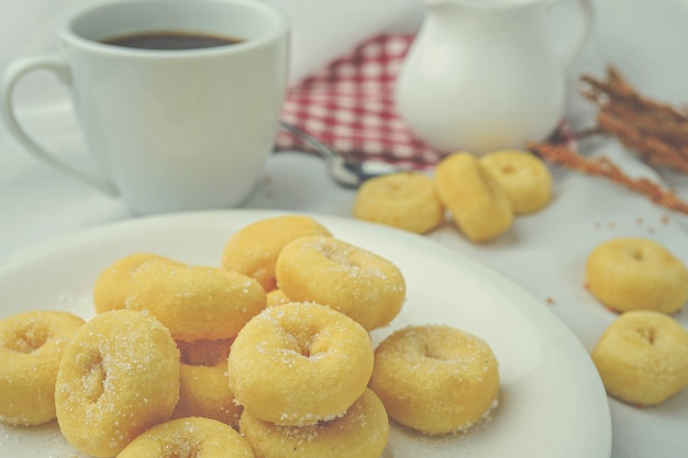 Mini donuts on white plate and a cup of coffee.