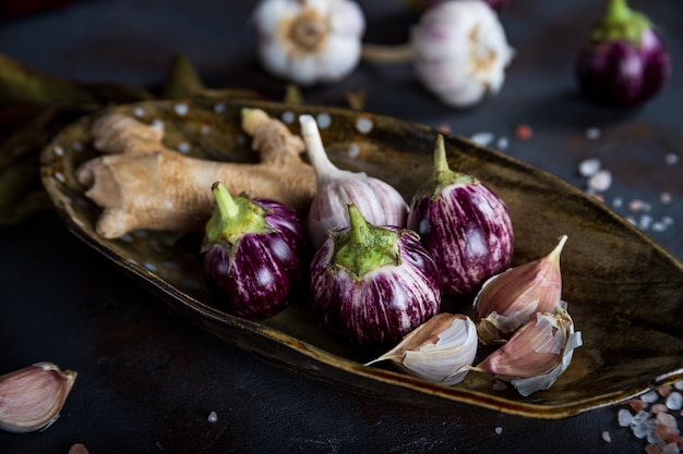 Mini eggplants, ginger, garlic in handmade ceramic plate, crystalline pink salt on concrete