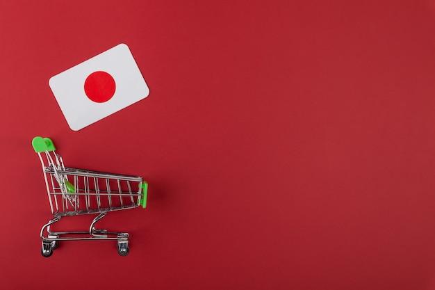 ミニ空のスーパーマーケットのショッピング食料品カート、赤い背景の上の日本の旗