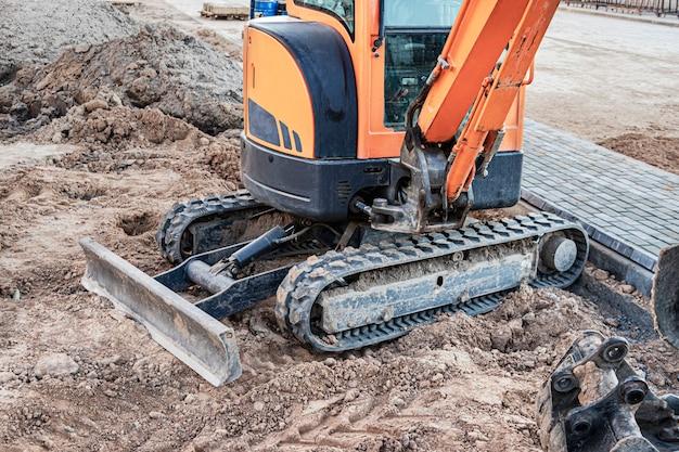 Мини-экскаватор на строительной площадке. компактная строительная техника для земляных работ.